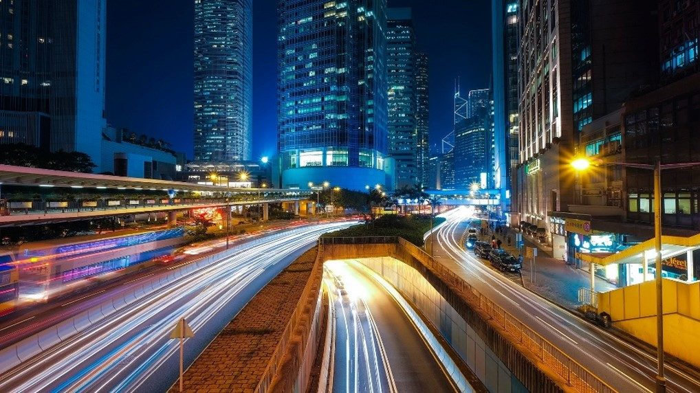 Geut befahrene Straße in einer Stadtumgebung bei Nacht