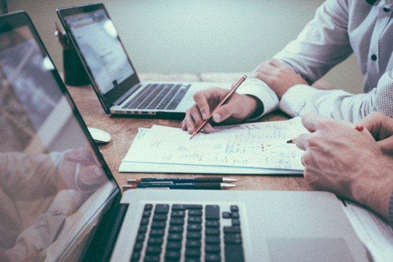 2 Laptops und eine Hand, die etwas auf einen Zettel schreibt