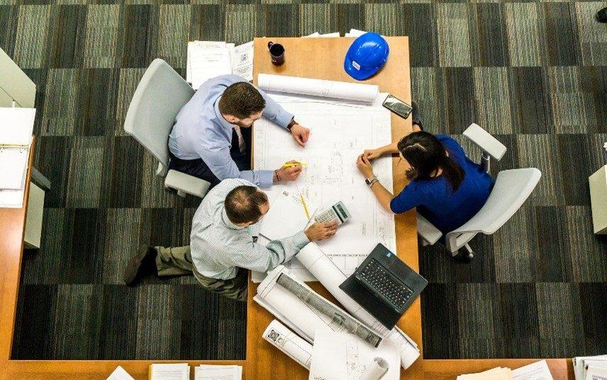 3 Männer sitzen an einem Tisch voll Papiere. Blickwinkel des Bildes von oben.