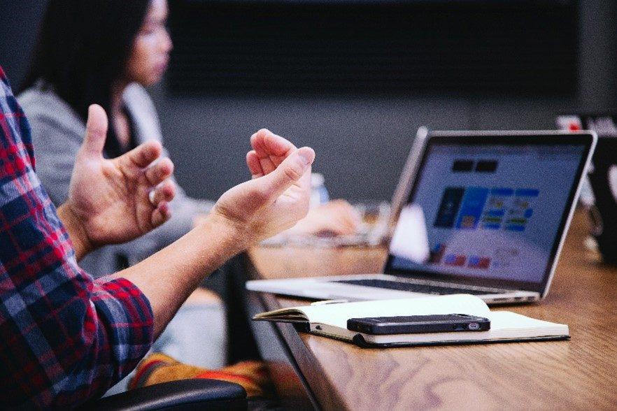 Hände in diskutierender Haltung vor Arbeitssetting