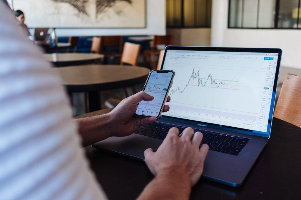 Mann vor Laptop und Handy